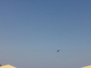 Вертолёт с пожарной ёмкостью  пролетает над отелем